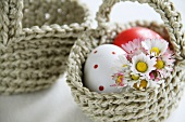 Little crocheted basket filled with eggs and daisies