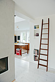 Old wooden ladder leaning on wall next to wide doorway showing view of modern kitchen beyond