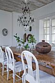 weiße Stühle an rustikalem Holztisch, darüber Kronleuchter mit Glasschmuck in ländlichem Esszimmer
