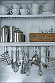 Crockery, stainless steel jugs and cooking utensils hanging from hooks on white shelves