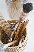 Basket holding paintbrushes, ink pens and coloured pencils