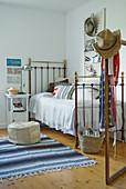 Metallbett im Vintagestil und gestreifter Teppichläufer auf Holzboden in ländlichem Schlafzimmer mit amerikanischem Flair