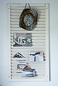 Weisser Jalousie-Fensterladen als Zeitschriftenhalter mit aufgehängtem Cowboyhut und Prospekten an Wand