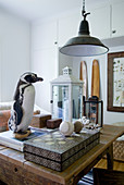 Stuffed penguin on stack of books, white lantern and board game on rustic wooden table below vintage pedant lamp