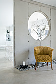 Bed of pebbles and vintage velvet armchair in front of exposed concrete partition wall with aperture