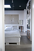 View into loft apartment bedroom with black ceiling - DIY bed made of white-painted pallets in front of exposed concrete partition