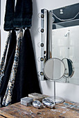 Moderner Badezimmerspiegel mit seitlicher Lichtleiste, alter Tisch mit Silberdöschen und schwarze Handtücher an der Wand hängend