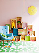Light blue, 50s retro armchair in front of DIY shelving made from wooden crates of various sizes
