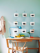 Kreatives Ordnungssystem - kleine Plastikeimer an Wandhaken über einem einfachem Schreibtisch mit 50er Jahre Armlehnstuhl