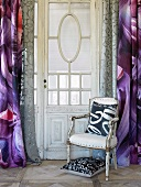 Upholstered chair with cushion in front of curtained window