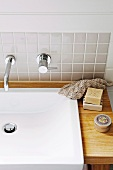 Modern vanity - sink with wooden counter and designer wall faucet on a tiled wall