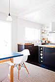 Open-plan kitchen with dark base units and dining area with white shell chairs