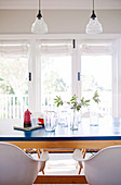 Dining table with blue top, white shell chairs and vintage glass pendant lamps