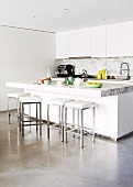 Open-plan, white designer kitchen with bar stools at breakfast bar