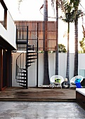 Stylish courtyard of contemporary house with white wicker chairs on wooden platform in front of palm trees and spiral staircase