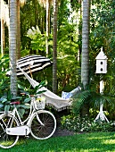 Bicycle, hammock strung between tropical trees, parasol and bird house
