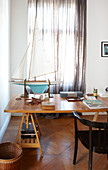 Model sailing boat on wooden table in front of window with closed, transparent curtains