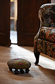 Armchair with floral upholstery and upholstered footstool in rustic setting