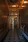 Grand hallway with arched doorway and painted wooden panelling on walls and ceiling