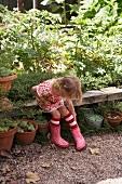 Little girl sitting on wooden bench in garden