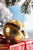 Gold Christmas tree ball ornament on a present