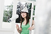 Young woman with newspaper hat and paint roller