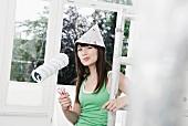 Junge Frau mit Papiermütze und Malerrolle