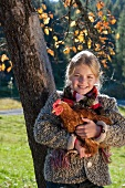Girl against a tree trunk holding a live hen