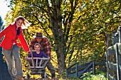 Parents pulling daughter through garden in handcart