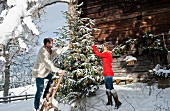 Young couple decorating Christmas tree in front of Alpine hut