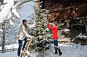 Junges Paar dekoriert schneebedeckten Christbaum vor einer Almhütte
