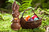 A chocolate bunny and a basket of Easter eggs in a forest