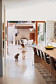 Little girl and dog in open-plan kitchen with plenty of seating at counter