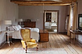 Antique armchair with gold upholstery in front of double bed in rustic setting with view into bathroom through open doorway