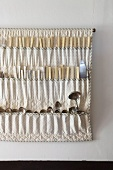 Vintage silver spoons in fabric cutlery holder hung on wall