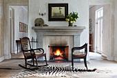Vintage Schaukelstuhl und antiker Stuhl auf Zebrafell vor Kaminfeuer in schlichtem Wohnhaus