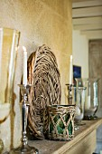 Lit candles in silver candlesticks and basketwork platter on wooden shelf