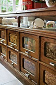 Breakfast crockery in traditional kitchen dresser with wood and glass drawer fronts