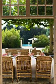 View through open terrace doors of wicker chairs at a set table with pool in Mediterranean garden in background
