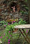 Old garden table and terracotta planter on chair; angel statue in niche of brick wall in background