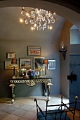 Elegant console table, framed pictures and crystal chandelier in foyer with terracotta floor tiles