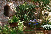 Rusty garden bench and garden table in front of brick wall
