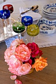 Posy of roses, lead crystal glasses and blue and white crockery on wooden table
