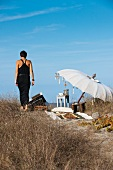 Seaside idyll with woman - seating area on beach with open parasol