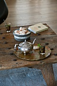 Oriental-style silver teapot and tea glass on tray on rustic wooden table