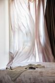 Bett vor verhülltem Fenster mit wehendem, luftigem Vorhang