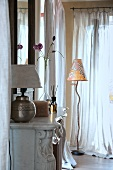 Table lamp on mantelpiece of grand open fireplace and modern standard lamp in corner of living room next to windows with airy curtains