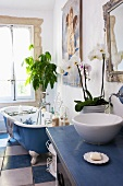 Bathroom with wooden washstand, free-standing bathtub and blue and white floor tiles