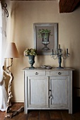 Stone vase and candelabra on wooden cabinet next to rustic standard lamp