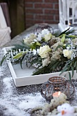 Flower arrangement in wintry colours with tealight